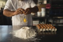Mid section of male baker preparing dough in bakery shop — Stock Photo