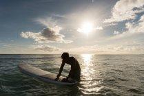 Mâle surfeur surf avec planche de surf dans la mer au crépuscule — Photo de stock