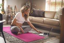 Беременная женщина использует ноутбук в гостиной на дому — стоковое фото
