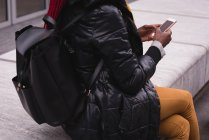 Середине раздел женщины, используя мобильный телефон в городе улица — стоковое фото