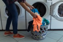 Gros plan de la femme faisant la lessive dans la laverie automatique — Photo de stock