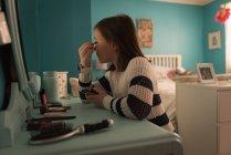 Girl applying eyeliner in bedroom at home — Stock Photo