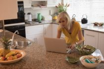 Worried senior woman checking her laptop in the kitchen at home — Stock Photo