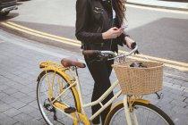 Bassa sezione di donna che tiene in bicicletta durante l'utilizzo del telefono cellulare sul marciapiede — Foto stock
