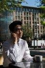 Jovem assumindo telefone celular no café ao ar livre — Fotografia de Stock