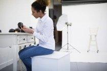 Fotógrafa revisando lente de cámara en estudio fotográfico - foto de stock