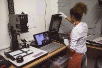 Female photographer using photo scanner in photo studio — Stock Photo