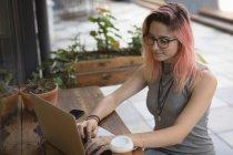 Молодая женщина с ноутбуком в кафе — стоковое фото