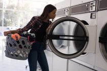 Young woman doing laundry in laundromat — Stock Photo