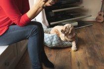 Mulher e animal de estimação cão sentado na sala de estar em casa — Fotografia de Stock