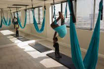 Woman exercising on swing sling hammock at fitness studio — Stock Photo