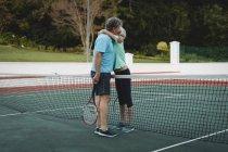 Senior pareja abrazándose en la cancha de tenis - foto de stock