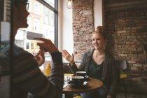 Junges Paar im Gespräch über den Kaffee im café — Stockfoto