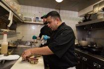 Мужчины шеф-повар готовит кусок курицы в кухне в ресторане — стоковое фото