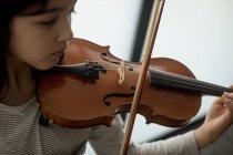 Adorabile studentessa giocare viloin nella scuola di musica — Foto stock