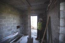 Ingeniero mirando el techo en el sitio de construcción - foto de stock