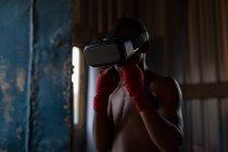 Мужской боксер, использующий гарнитуру виртуальной реальности во время занятий боксом в фитнес-студии — стоковое фото
