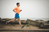 Young man jogging on he sea shore — Stock Photo