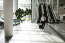 Businessman walking with suitcase in office — Stock Photo