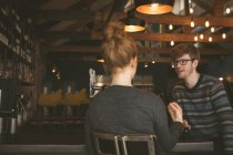 Молода пара говорити один з одним в барна стійка — стокове фото