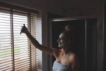 Женщина с кремом для лица делает селфи с мобильным телефоном в ванной комнате дома — стоковое фото