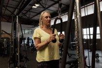 Mulher com deficiência exercer na máquina no ginásio — Fotografia de Stock