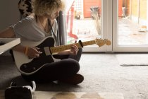 Young woman playing guitar in living room at home — Stock Photo