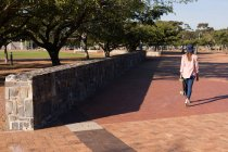 Rear view of woman walking in the park with skateboard — Stock Photo