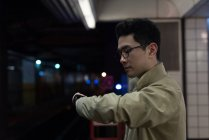 Young man checking time at railway station — Stock Photo