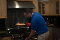 Man preparing pizza in the kitchen at home — Stock Photo