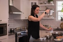 Woman holding jug of milk in kitchen at home — Stock Photo