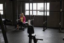 Disabled mature woman using mobile phone in the gym — Stock Photo