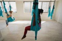 Deux femmes de se détendre dans le hamac sling balançoire au studio de remise en forme — Photo de stock