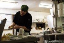 Мужчина-повар, подающий еду в тарелке в ресторане — стоковое фото