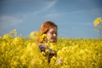 Head shot of woman touching crops in the mustard field on a sunny day — Stock Photo