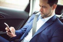 Homme d'affaires intelligent à l'aide de téléphone portable dans une voiture — Photo de stock