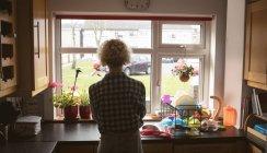 Donna che guarda attraverso la finestra in cucina a casa — Foto stock