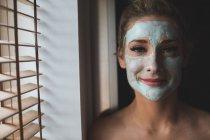 Donna con crema per il viso nel bagno di casa — Foto stock