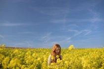 Woman touching crops in the mustard field on a sunny day — Stock Photo
