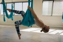 Женщина, упражнения на гамак качели Слинг на фитнес-студии — стоковое фото