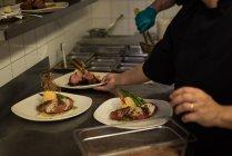 Sección media del hombre chef sirviendo comida en un plato - foto de stock