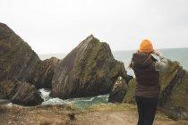 Junge Wanderin blickt mit Fernglas aufs Meer — Stockfoto