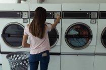 Young woman operating washing machine at laundromat — Stock Photo