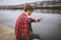 Giovane che usando il suo telefono mobile al porto — Foto stock