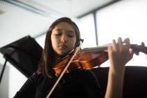 Adorable colegiala tocando violín en la escuela de música - foto de stock