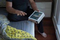 Sección media del hombre usando tableta digital en el dormitorio en casa - foto de stock