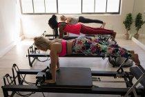 Gruppe von Frauen, die auf spannmaschine im Fitness-Studio trainieren — Stockfoto