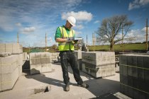 Ingeniero escribiendo en el bloc de notas en el sitio de construcción en un día soleado - foto de stock