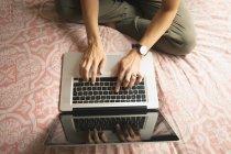 Vista aérea de la mujer usando el ordenador portátil en la cama en el dormitorio en casa - foto de stock