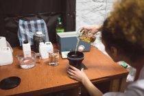 Женщина-фотограф заливает химикат на обложку объектива в фотостудии — стоковое фото